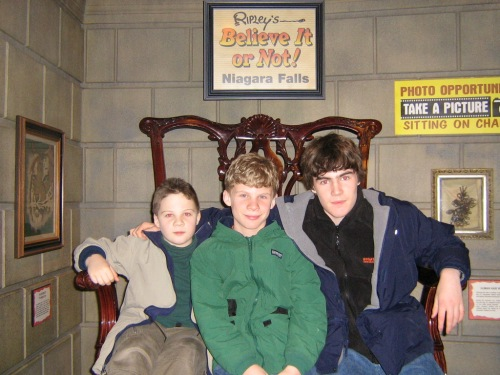 the boys take advantage of a photo op in a chair made for the biggest man ever