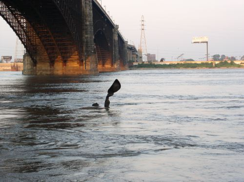 """Here is an ironic photo of """"The Captain's Return"""" statue on the flooded riverfront."""
