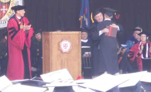 proud papa bestows the diploma as the president looks on