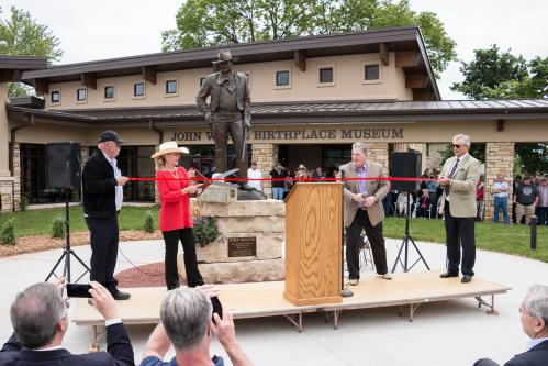 Cutting the ribbon during the grand opening ceremony for the John Wayne Birthplace Museum in Winterset. Left to right: Barry Corbin (actor & Birthplace board member), Aissa Wayne (John Wayne's daughter), Joe Zuckschwerdt (Birthplace & Museum President), and Christopher Mitchum (actor). 5/23/2015 Photo by John Pemble